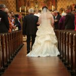 Bride and father walk up Isle